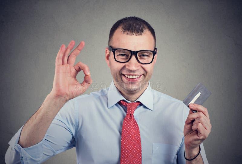 Rozochocony szczęśliwy biznesowy mężczyzna z kartą kredytową pokazuje Ok znaka zdjęcia royalty free