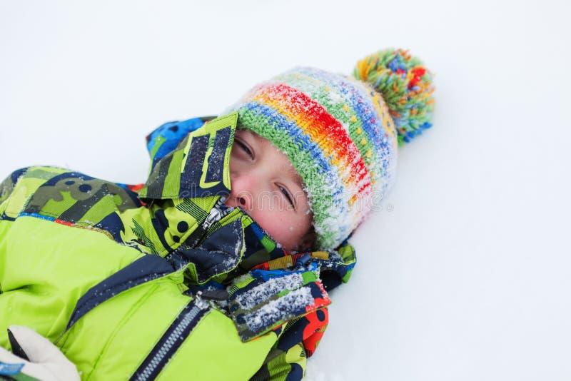Rozochocony szczęśliwy chłopiec kłamstwo na śniegu, zdjęcie stock