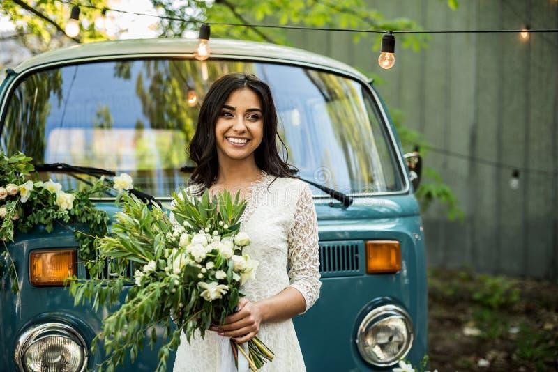 Rozochocony szczęśliwy młody panna młoda chwyta bukiet blisko minibusa Zakończenie obraz stock