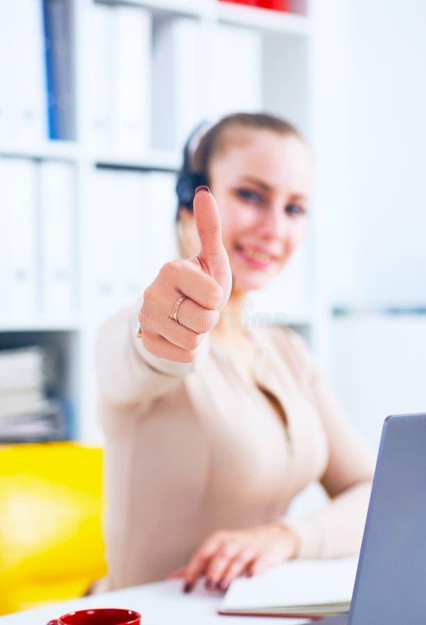Rozochocony uśmiechnięty żeński obsługa klienta operator pokazuje aprobaty w biurze zdjęcia stock