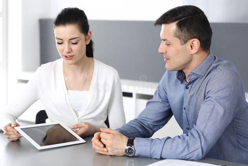 Rozochocony uśmiechnięty biznesmen i kobieta pracuje z pastylka komputerem w nowożytnym biurze Headshot przy spotkaniem lub miejs obrazy stock