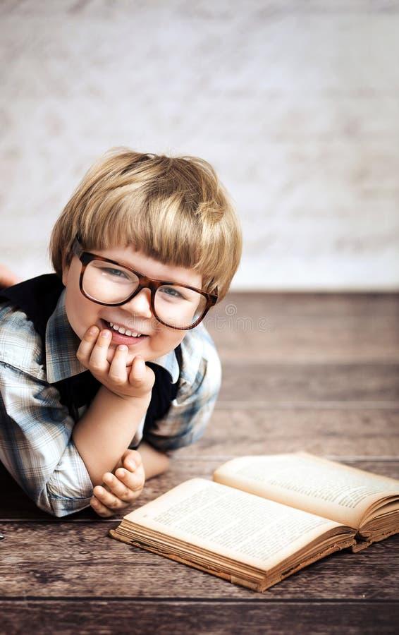 Rozochocony uśmiechnięty małe dziecko czyta książkę zdjęcia stock