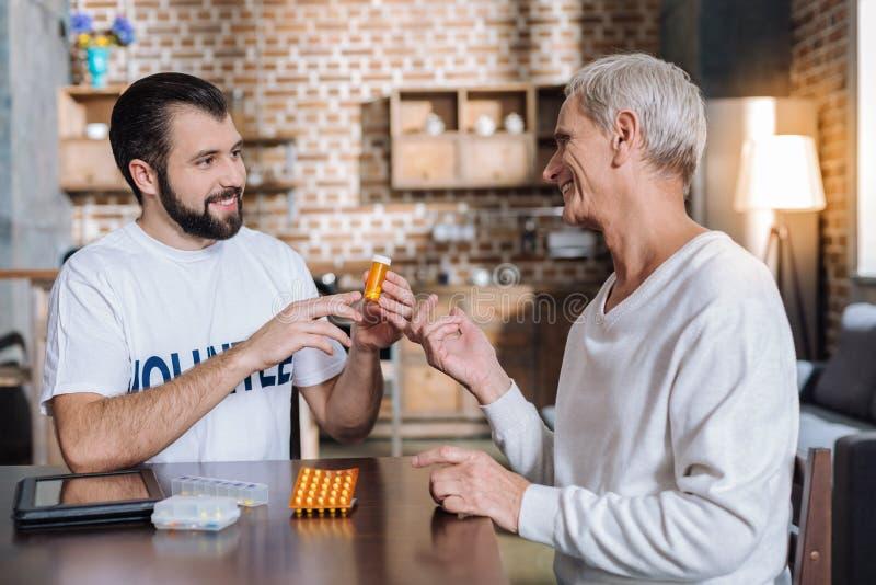 Rozochocony uśmiechnięty starszy mężczyzna komunikuje z miłym pracownikiem opieki społecznej obraz stock
