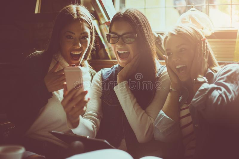 Rozochocony uczeń dziewczyny obsiadanie w bibliotece i używać telefonie komórkowym obraz stock