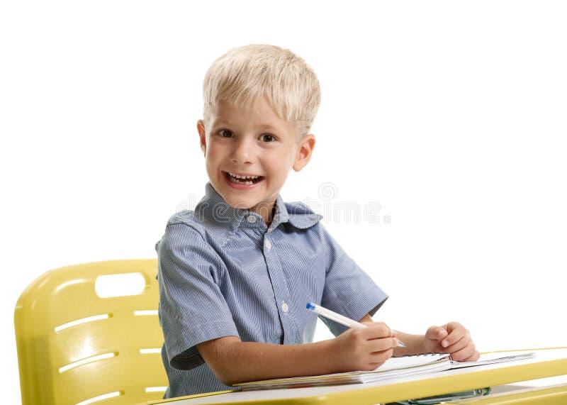 Rozochocony uczeń przy biurkiem zdjęcia stock