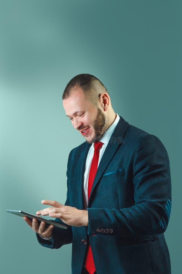Rozochocony ufny biznesmen trzyma cyfrową pastylkę, jest u obraz royalty free