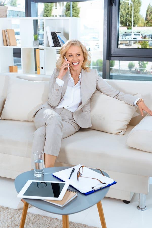 rozochocony w średnim wieku bizneswoman opowiada na smartphone obrazy royalty free