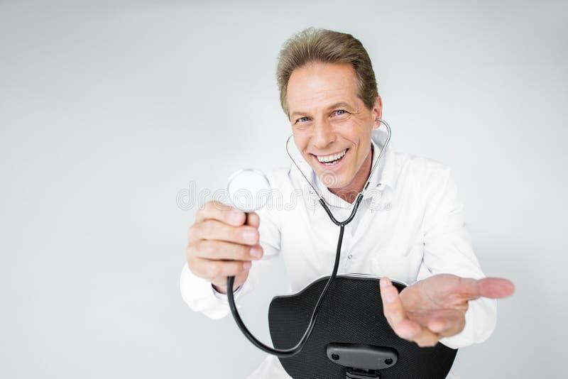 rozochocony w średnim wieku doktorski mienie stetoskop podczas gdy siedzący na krześle fotografia stock