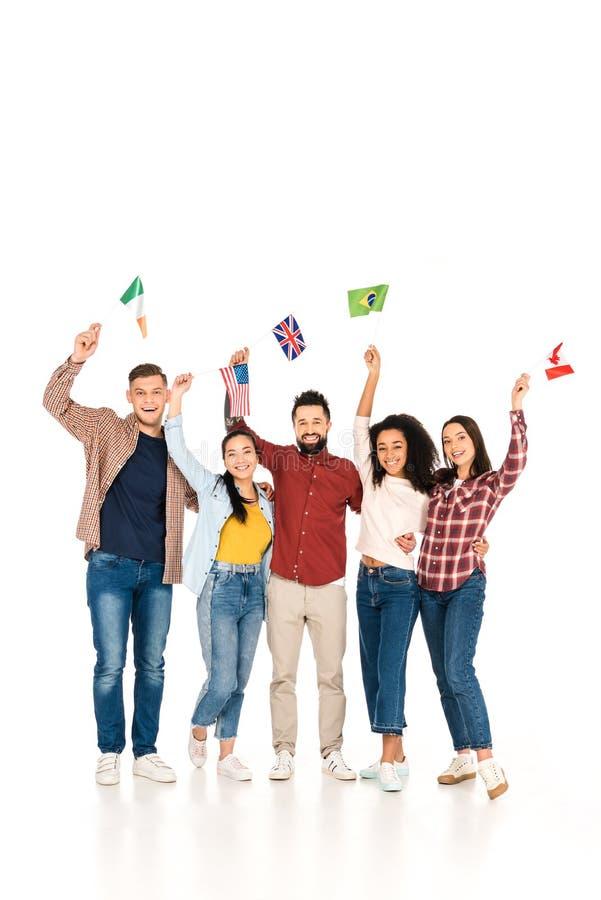 rozochocony wielokulturowy grupa ludzi ono uśmiecha się z flagami różni kraje nad głowy odizolowywać obraz stock