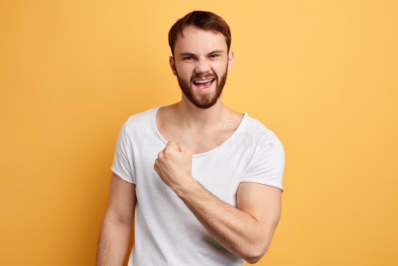 Rozochocony z podnieceniem szczęśliwy mężczyzna jest ubranym białego koszulki odświętności zwycięstwo zdjęcia stock