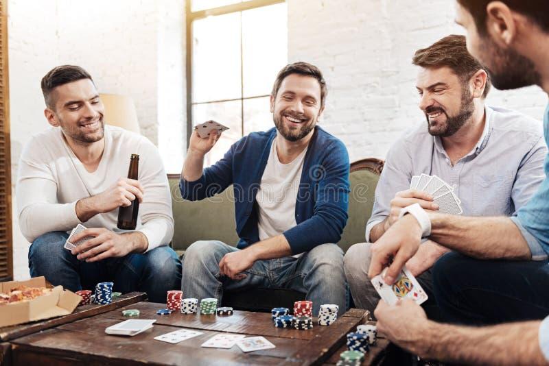 Rozochocony zadowolony mężczyzna stawia jego karty na stole zdjęcia royalty free
