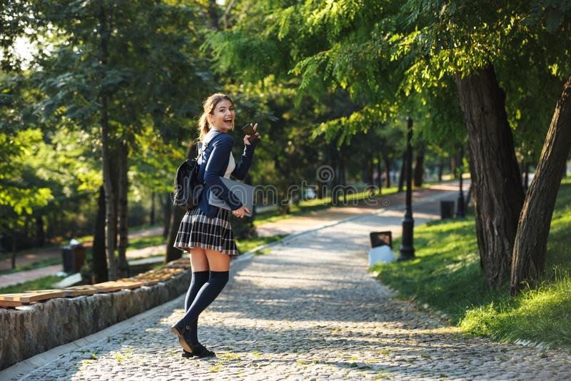 Rozochoconych potomstw szkolna dziewczyna chodzi outdoors obraz royalty free