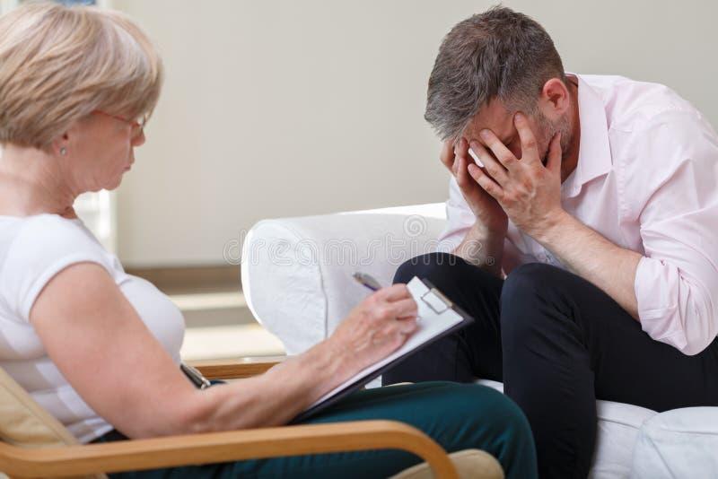 Rozpacz młoda samiec z terapeuta zdjęcia stock