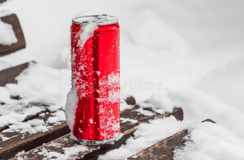Rozpieczętowana czerwona błyszcząca jaskrawa blaszana puszka z białym śniegiem na swój powierzchni z kluczem dla chłodno zimnych  fotografia stock