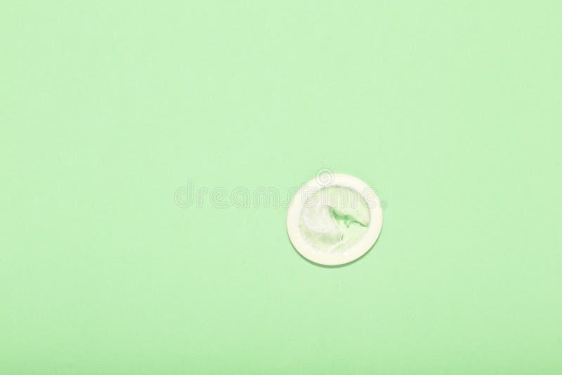 Rozpieczętowany kondom i kondom w paczce na zielonym tle royalty ilustracja