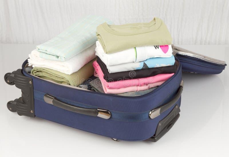 Rozpieczętowana walizka pakująca z mnóstwo kolorowymi płótnami obraz royalty free