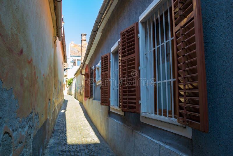 Rozpieczętowane drewniane żaluzje wyjawia zamkniętych białych nadokiennych bary na wąskiej ulicie w Sibiu Hermannstadt, Rumunia zdjęcie stock
