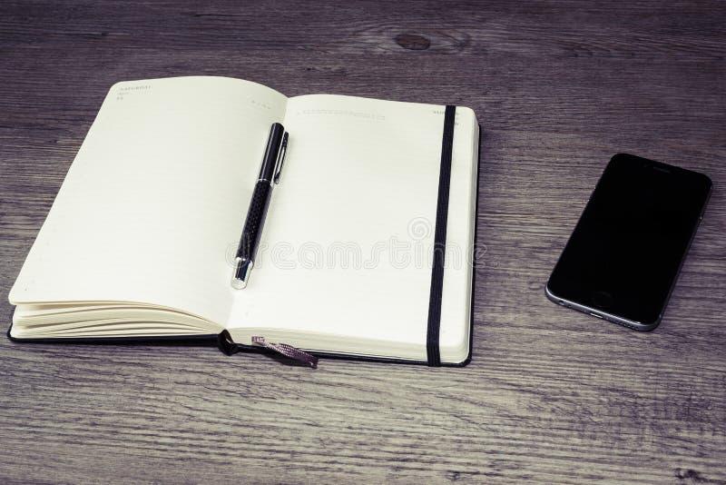 Rozpieczętowany kalendarz, dzienniczek z piórem lub telefon komórkowy na drewnianym stole obrazy royalty free