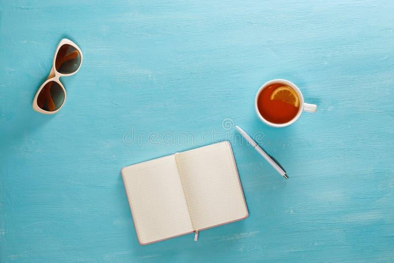 Rozpieczętowany notatnik z piórem, filiżanka herbata i okulary przeciwsłoneczni na błękitnym drewnianym stole, Odgórny widok Pisa fotografia royalty free