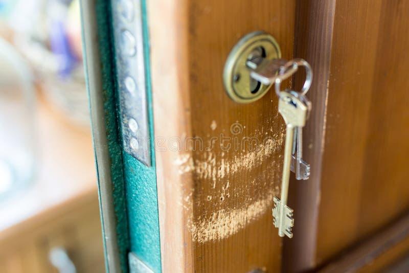 Rozpieczętowany opancerzony drzwi z keychain w kędziorku Porysowana drewniana część pod wiązką klucze zdjęcie stock