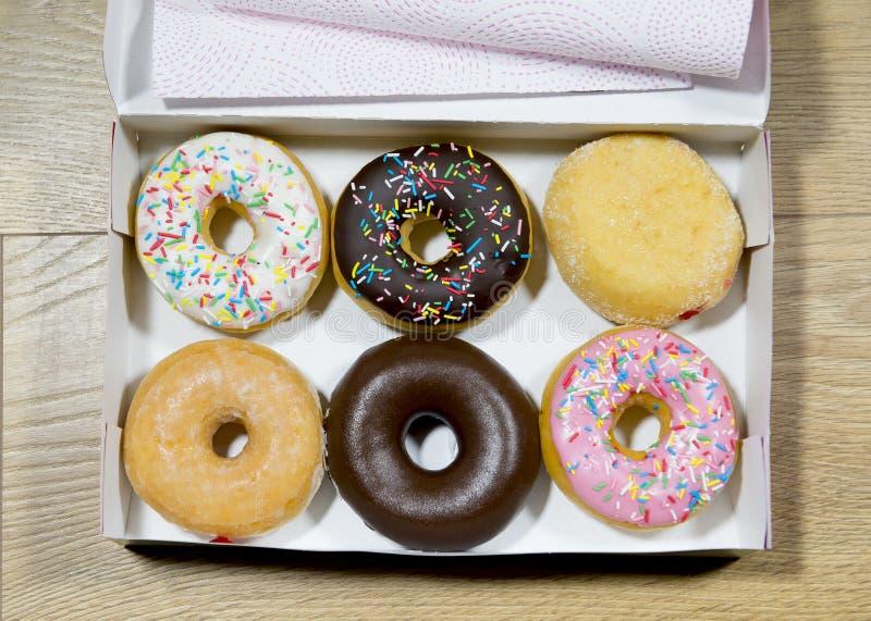 Rozpieczętowany pudełko z pączkiem ustawiającym w różnorodnych smakach tak jak czekoladowe truskawkowe śmietanki i cukierku polew obrazy stock