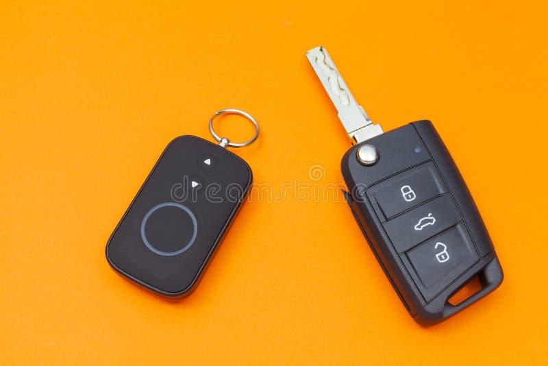Rozpieczętowany samochodu klucz z pilotem do tv na pomarańczowym tle, odgórny widok zdjęcie royalty free