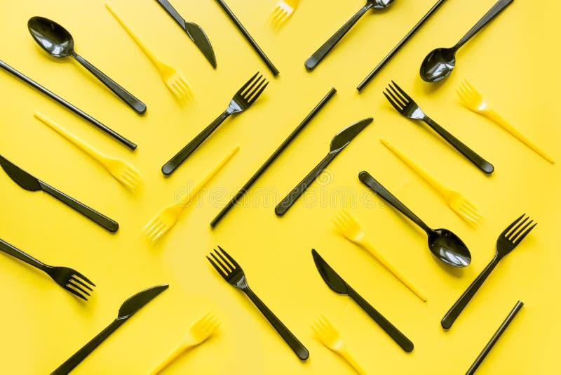 Rozporządzalny pykniczny czarny nóż i rozwidlenia w przekątnie na kolorze żółtym Odg?rny widok Mieszkanie nieatutowy fotografia stock