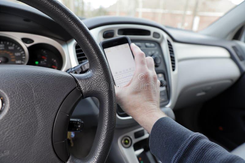 Rozpraszający uwagę kierowca z telefonem w ręce, pojazdu wnętrze zdjęcia royalty free