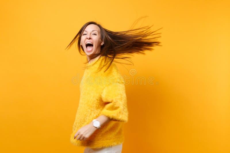 Rozradowana komiczna młoda dziewczyna w futerkowym puloweru bielu dyszy kłębienie błaź się wokoło w pracownianym doskakiwaniu z t obrazy stock