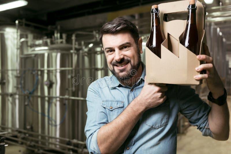 Rozradowane mężczyzna mienia butelki alkohol w browarze fotografia royalty free