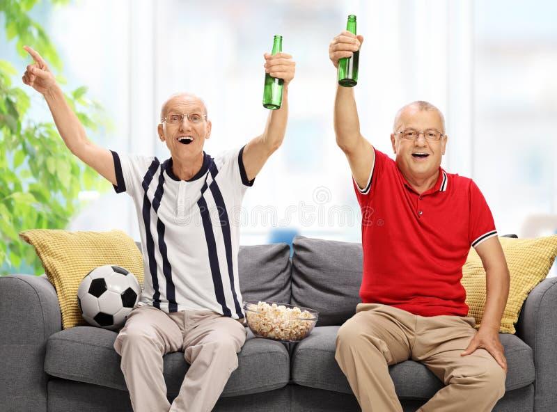 Rozradowani seniory sadzający na kanapy dopatrywania cheerin i futbolu obrazy royalty free