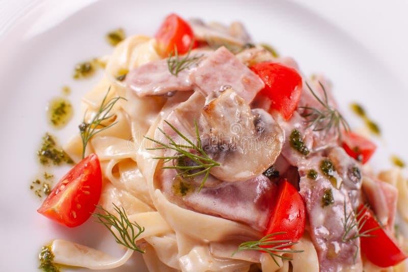 rozrasta się tagliatelle Włoski makaron na bielu talerzu z szampinionami, baleronem i pomidorem, zdjęcia royalty free