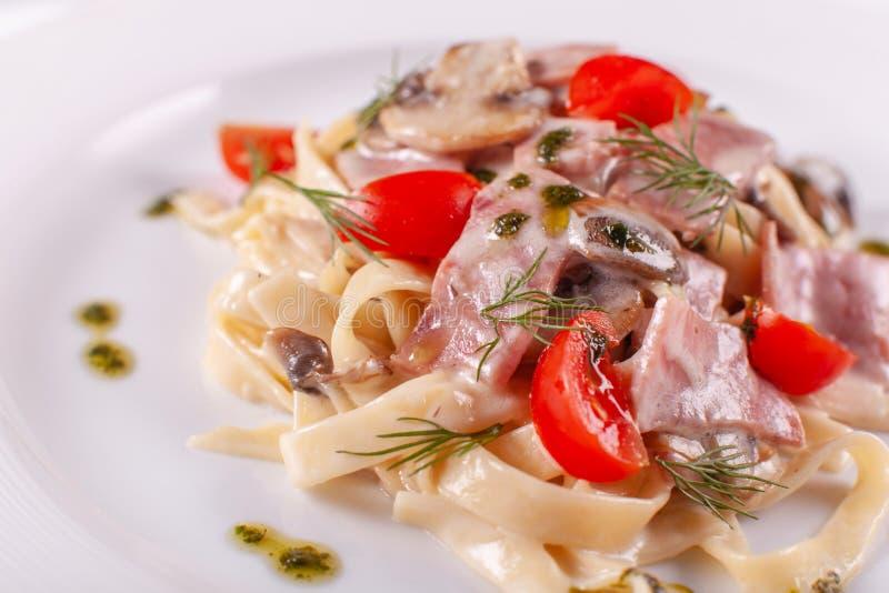 rozrasta się tagliatelle Włoski makaron na bielu talerzu z szampinionami, baleronem i pomidorem, zdjęcie stock
