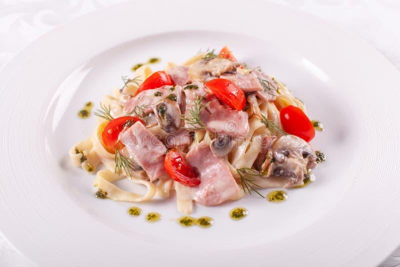 rozrasta się tagliatelle Włoski makaron na bielu talerzu z szampinionami, baleronem i pomidorem, fotografia stock