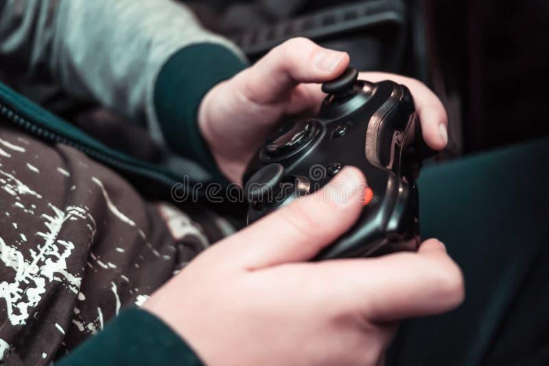 Rozrywka, domowe elektronika, hazardu pojęcie: nastolatek wręcza mieniu bezprzewodowego kontrolera gamepad bawić się konsolę wide zdjęcia stock