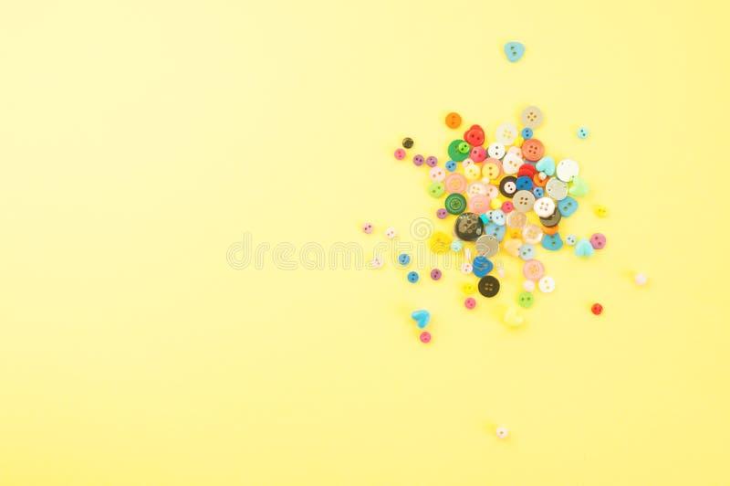 Rozrzucanie kolorowi guziki i koraliki na żółtym backgroun zdjęcie royalty free