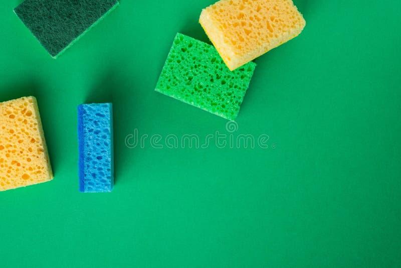 Rozrzucony kolor żółty, zieleń, błękitne gąbki na zieleń barwiącym papierowym tle, kopii przestrzeń, odgórny widok, mieszkanie ni obraz stock