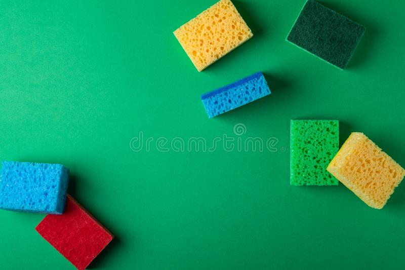 Rozrzucony kolor żółty, zieleń, czerwień, błękitne gąbki na zieleń barwiącym papierowym tle, kopii przestrzeń, odgórny widok, mie obraz royalty free