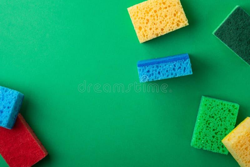 Rozrzucony kolor żółty, zieleń, czerwień, błękitne gąbki na zieleń barwiącym papierowym tle, kopii przestrzeń, odgórny widok, mie obraz stock