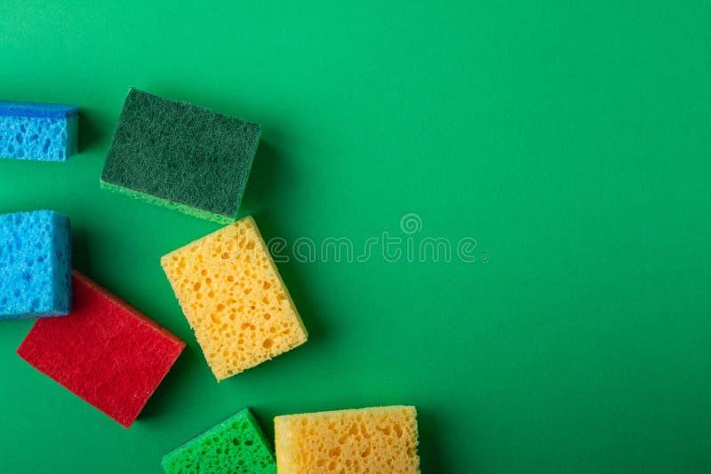 Rozrzucony kolor żółty, zieleń, czerwień, błękitne gąbki na zieleń barwiącym papierowym tle, kopii przestrzeń, odgórny widok, mie zdjęcia stock