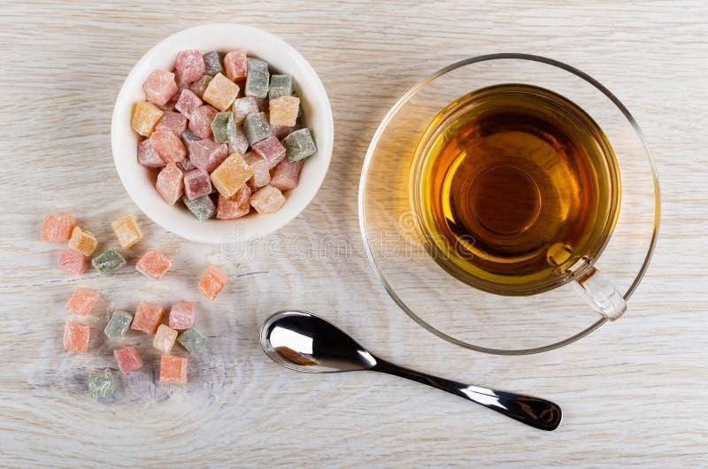 Rozrzucony rakhat-lukum, puchar z rakhat-lukum, filiżanka herbata na spodeczku, teaspoon na stole fotografia stock