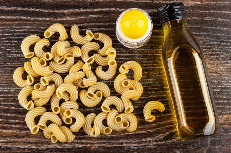 Rozrzucony surowy makaronu cavatappi, sól, butelka jarzynowy olej na drewnianym stole Odg?rny widok obrazy stock