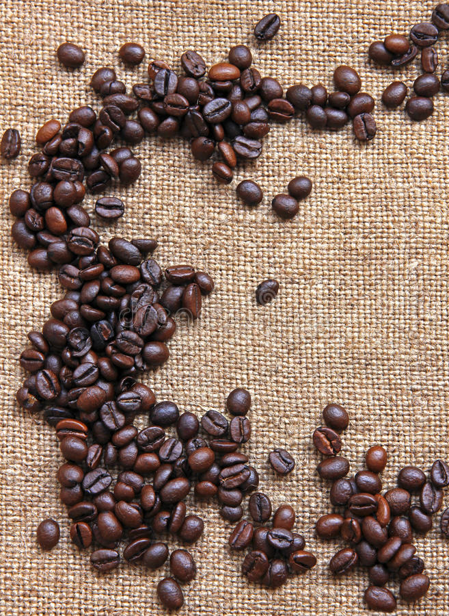 Rozsypisko burnt kawowe fasole na parcianym tle obraz stock