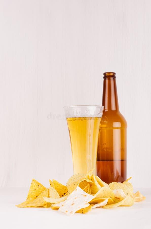 Rozsypisko dżonki piwne przekąski i złoty lager piwo w szkle, brown butelka na miękkim białym drewnianym tle zdjęcie royalty free