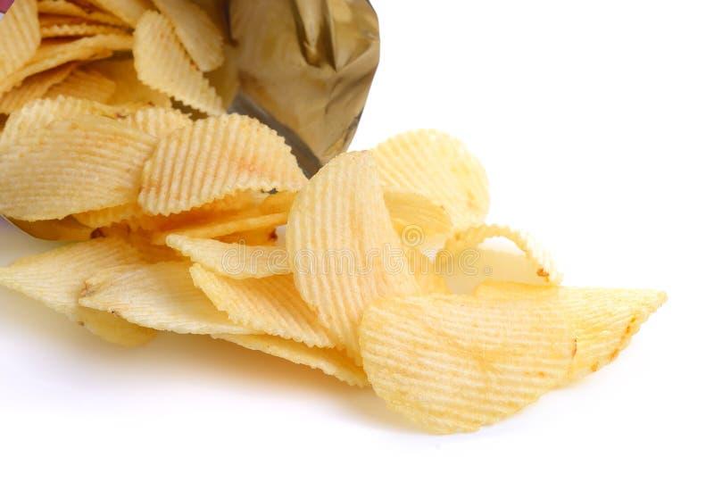 Rozsypisko kartoflani chipsy na białym tle obraz stock