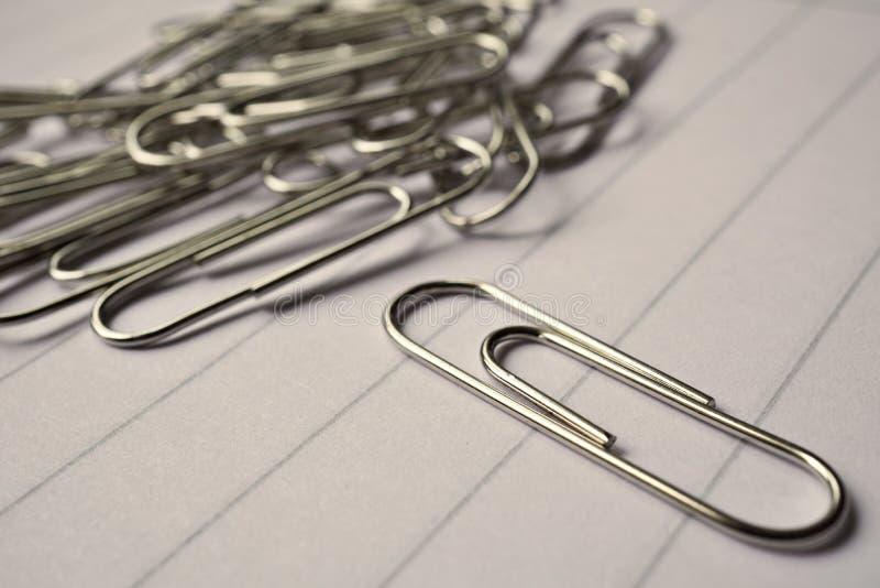 Rozsypisko metal papierowe klamerki na białym prążkowanym papierowym notepad jako symbol typowy biurowy środowisko obraz royalty free