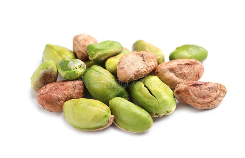 Rozsypisko obrane organicznie pistacjowe dokrętki na białym tle zdjęcia stock