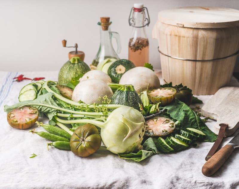 Rozsypisko różnorodni zieleni warzywo składniki na lekkim kuchennym stole Zdrowy ?asowanie i kucharstwo Czyści jarskiego jedzenie fotografia stock