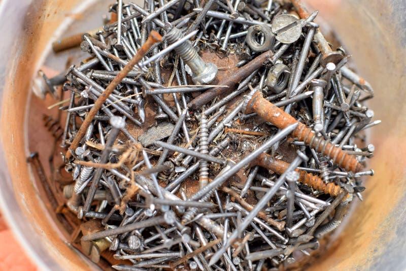 Rozsypisko starzy ośniedziali gwoździe i śruby na dnie puszka zdjęcie stock