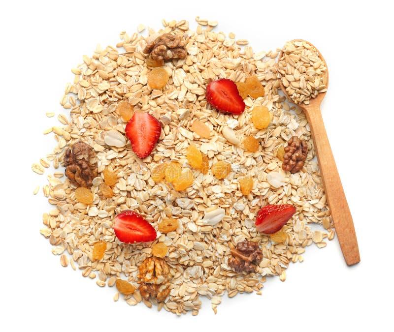 Rozsypisko surowy oatmeal z rodzynkami, orzechem włoskim i truskawką na białym tle, obraz stock